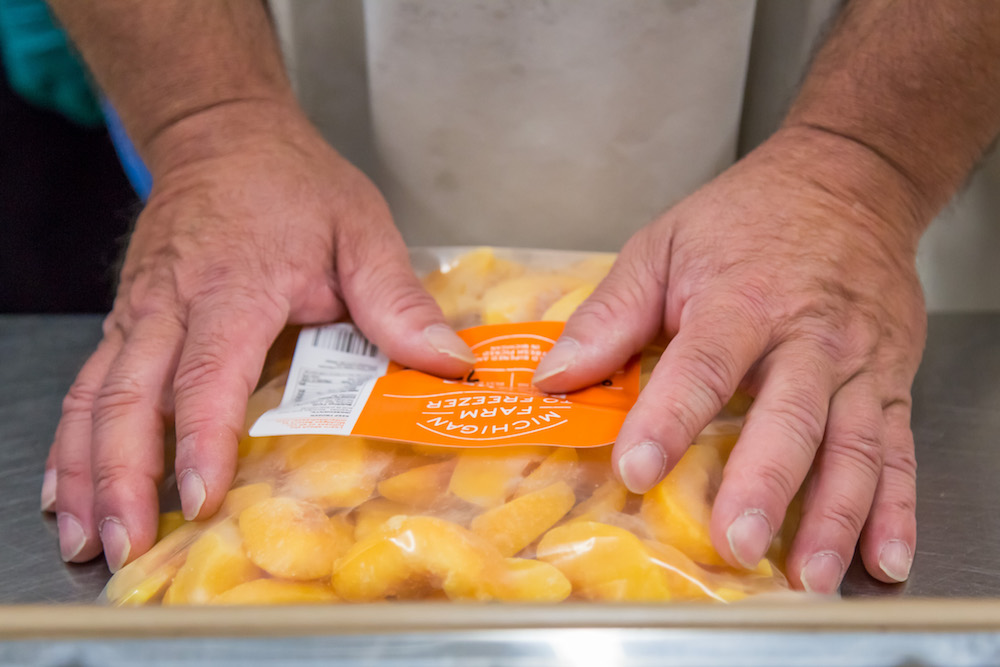 A Michigan Farm to Freezer team member packs up IQF peaches at the Traverse City facility.